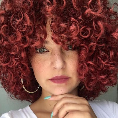 woman with red curly hair with highlights.