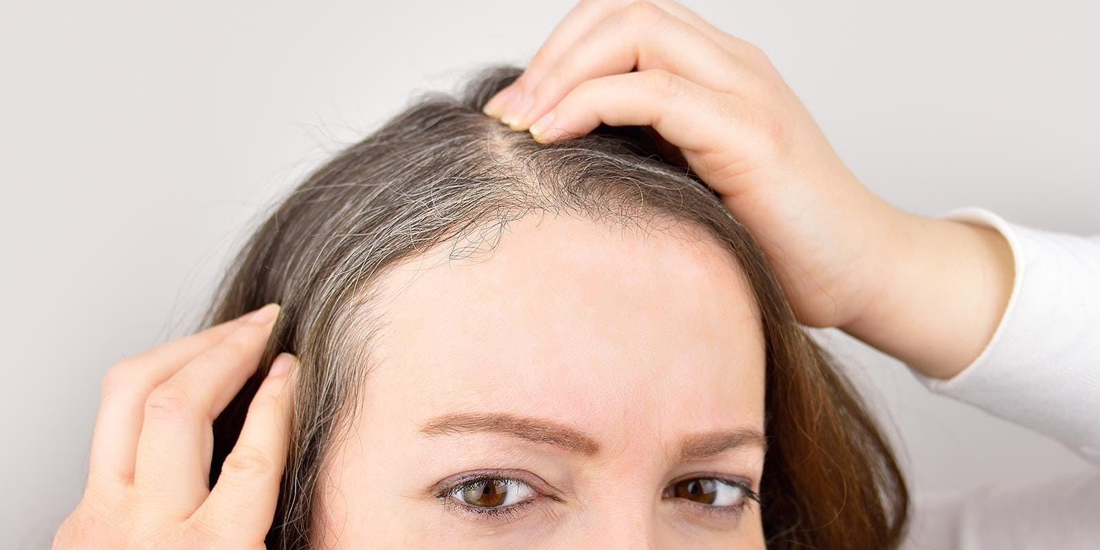 Is your hair color making you look older? (woman examining her hair)