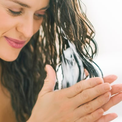 Woman applying conditioner to her hair